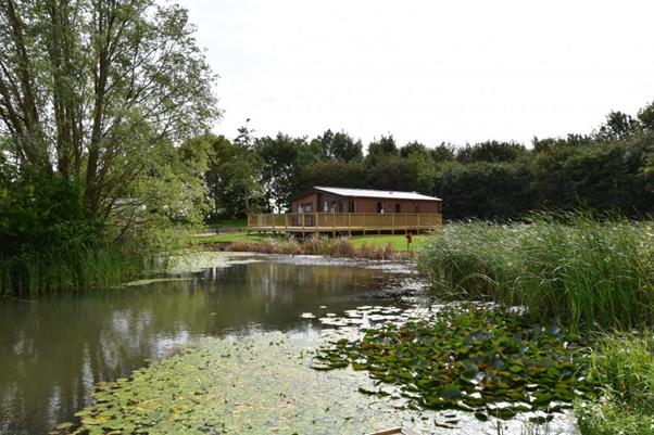 A caravan overlooking greenery and one of the lakes at Brickyard Lakes' static caravan site