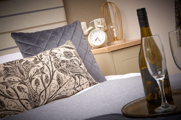 A bed with cushions, alarm clock and bottle of wine with glasses inside a Brickyard Lakes holiday lodge in North Yorkshire